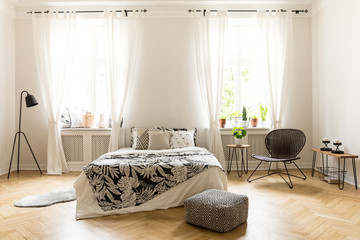 Real photo of a cozy bedroom interior with a double bed, pouf, lamp, windows and chair