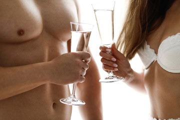 Happy tender young couple drinking champagne together at home