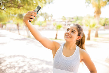 Woman taking selfie at park after a run