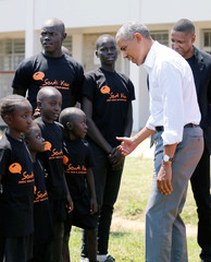 Former U.S. President Barack Obama meets children as he tours the Sauti Kuu resource centre near his ancestral home in Nyangoma Kogelo village in Siaya county