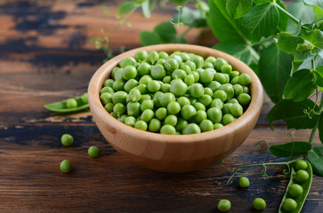 Fresh organic green peas on rustic wooden background.
