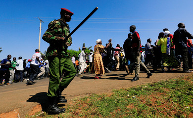 A riot policeman disperses residents chanting slogans on the road during the visit by Former U.S. President Barack Obama to his ancestral Nyangoma Kogelo village in Siaya county