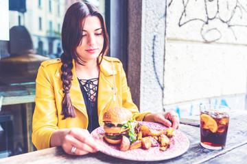 Young woman sitting outdoor restaurant eating an hamburger- hunger, food, meal concept