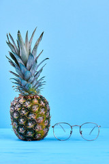 Fresh organic pineapple and eyeglasses. Whole ripe ananas and eyeglasses placed on blue wooden surface, vertical image.