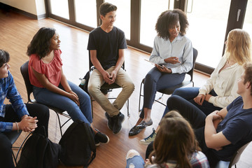Female Tutor Leading Discussion Group Amongst High School Pupils