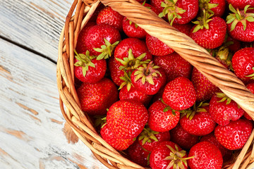 Basket full of fresh strawberries. Ripe juicy strawberries in wicker basket, top view. Healthy nutritious berries.