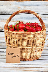 Fresh strawberries in wicker basket. Juicy strawberries and craft card with text love you. Idea of love confession.