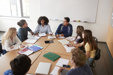 Female High School Tutor Sitting At Table With Pupils Teaching Maths Class