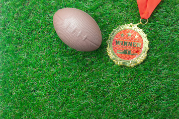 Table top view aerial image soccer or football season background.Flat lay accessories american ball and gold medal on the artificial green grass wallpaper.Free space for design text and content.