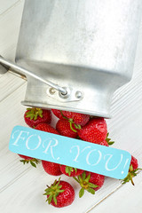 Fresh strawberries and romantic paper message. Ripe juicy strawberries, metal bucket and turquoise card with text for you. Love and romance.