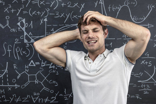 portrait of a student near the blackboard holding his arms to his head in a sign of stress and disappointment. concept of study and learning difficulties.