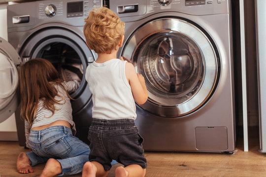 Kids playing with washing machine at home