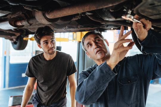 Two mechanics repairing a car.