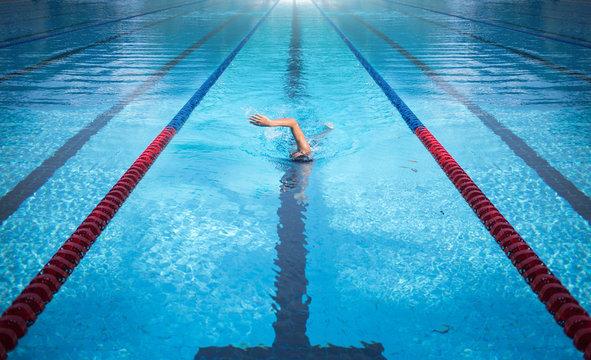 one man swimming on swimming pool lane