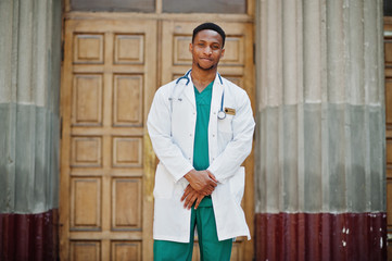 African american doctor male at lab coat with stethoscope outdoor against clinic door.
