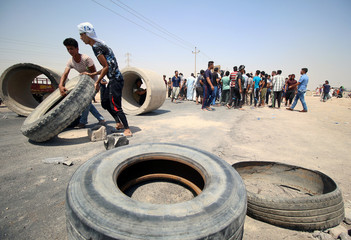 Iraqi protesters move tires and concrete blocks to block the road during a protest in south of Basra