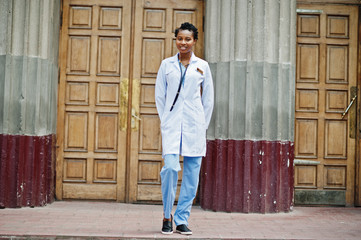 African american doctor female at lab coat with stethoscope outdoor against clinic door.
