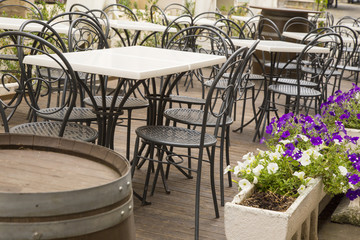 tables and chairs in black iron of an outdoor bar with vases of white and purple flowers