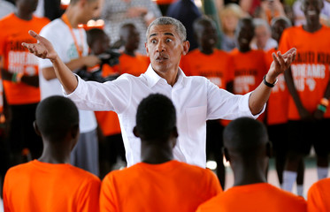 Former U.S. President Barack Obama reacts as he addresses players at the basketball court during the launch of Sauti Kuu resource centre near his ancestral home in Nyangoma Kogelo village in Siaya county