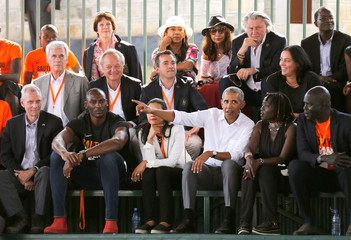 Former U.S. President Barack Obama seats with delegates at the basketball court during the launch of Sauti Kuu resource centre near his ancestral home in Nyangoma Kogelo village in Siaya county