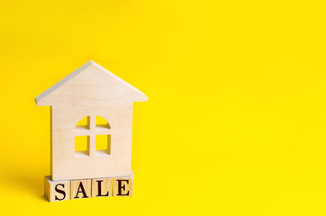 """wooden house on a yellow background with the inscription """"sale"""". sale of property, home, real estate. affordable housing. place for text. copyspace"""