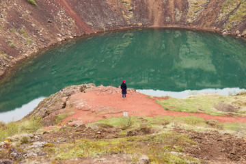 Woman on the precipice of the volcano crater in Iceland