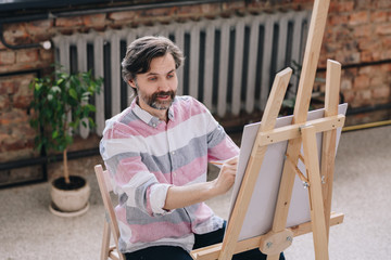 Portrait of handsome mature man  painting sitting by easel in art class and smiling, enjoying work in spacious sunlit loft studio, copy space