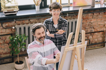 Portrait of smiling mature man painting sitting by easel in art studio with female art teacher watching him in art class, copy space