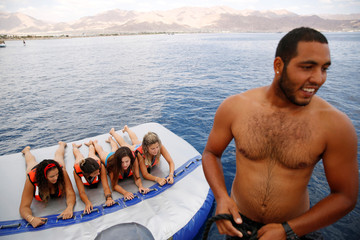 Teenagers hold onto an inflatable water sport raft in the Red Sea, in Eilat