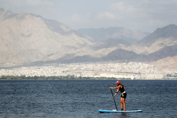 A woman paddles as she stands on a surfboard in the Red Sea, off Eilat's shore