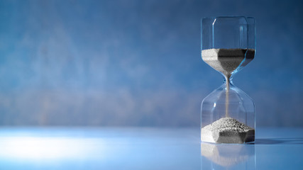 Sliver sand running through the shape of modern hourglass on white table.Time passing and running out of time. Urgency countdown timer for business deadline concept