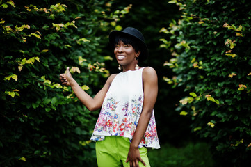 Amazing african american model woman in green pants and black hat posed with different emotions at park, shows a thumb up.