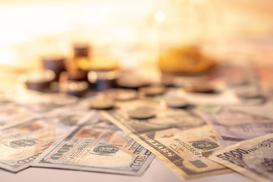 Various of international money coin and banknote with blurred hourglass in the background. Time investment with currency exchange concept. Focus on dollar banknote.