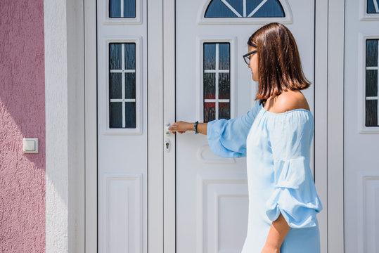 Front door. girl or young woman holds doorknob on front door PVC