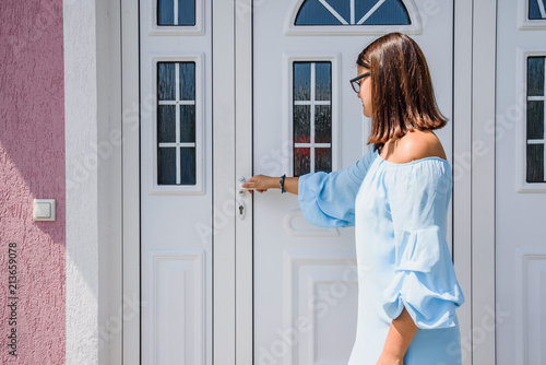 Front Door Girl Or Young Woman Holds Doorknob On Front Door Pvc