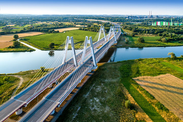 Fotorollo Bridges New modern double cable-stayed bridge over Vistula River in Krakow, Poland. Part of the ring motorway around Krakow under construction. Aerial view at sunset. Sedzimir Steelworks in the background.