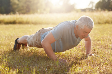 Exercise, fitness, age and workout concept. Healthy sporty mature male has physical exercises outdoor in early morning, makes plank on ground, expresses his determination and desire to be fit