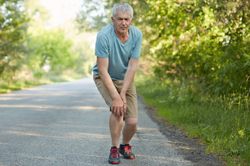 Full length portrait of displeased male pensioner, leans on knees, has pain after jogging, banged his leg, stands on road in rural area, being sporty in his fifties. People and fitness concept