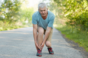 Attractive grey haired elderly male pulled muscle of leg, suffers from pain, can`t continue jogging, dressed in casual outfit, wears sneakers, poses on road in urban area. People, flexibility concept