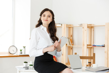 Happy young business woman or secretary holding document in modern office