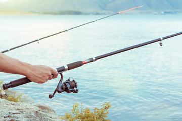 hand with spinning and reel on summer lake. two fishing rods catching fish