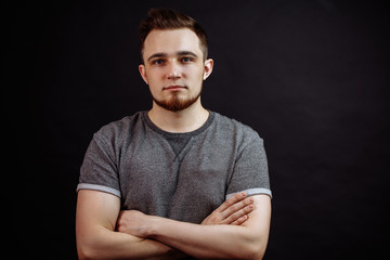 Portrait of attractive young male in grey t-shirt standing with crossed arms isolated on black background.
