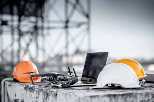 Drone, remote control, smartphone, laptop computer and protective helmet at construction site. Using unmanned aerial vehicle (UAV) for land and building site survey in civil engineering project.