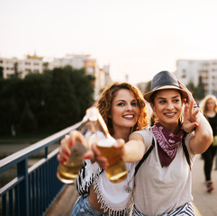 Portrait of a two party girls drinking and cheering in the summer.
