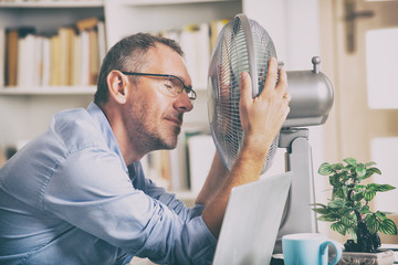 Man suffers from heat in the office or at home