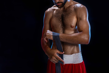 Boxer preparing her gloves for a fight. Photo of muscular man strapping up hands on black background.