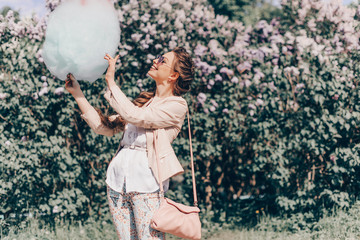 Portrait of a Smiling Beautiful Lady in Sunglasses Holding Cotton Candy at Park and Happily Looking in Camera. Film Color and Toning