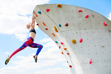 Photo from below of sports woman in leggings hanging on wall for climbing against blue sky