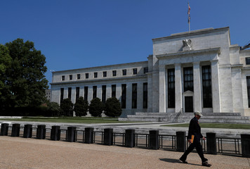 People walk past the Federal Reserve building in Washington, U.S.