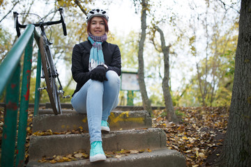 Photo of girl sitting on stairs next to bicycle